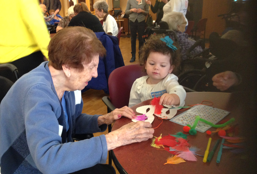 Little-ones create Purim mask crafts with the help of Bubbies and Zadies at Hillel Lodge.
