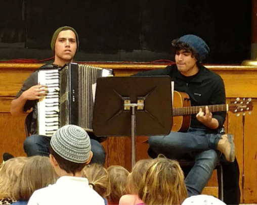 One young man playing an accordian and one playing a guitar with a music stand in front of them