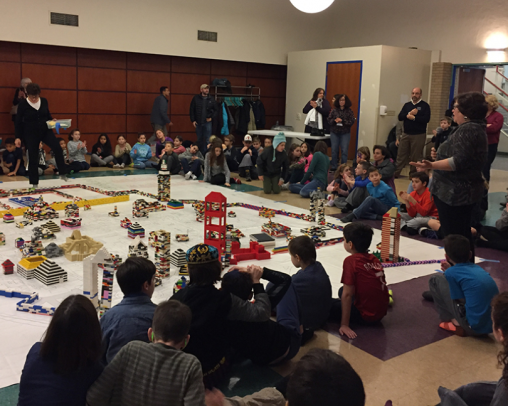 A room full of children and adults with a village in the middle built out of legos