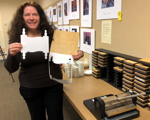 A local teacher in the CCJE Room holding a Torah outline made from the di-cut machine