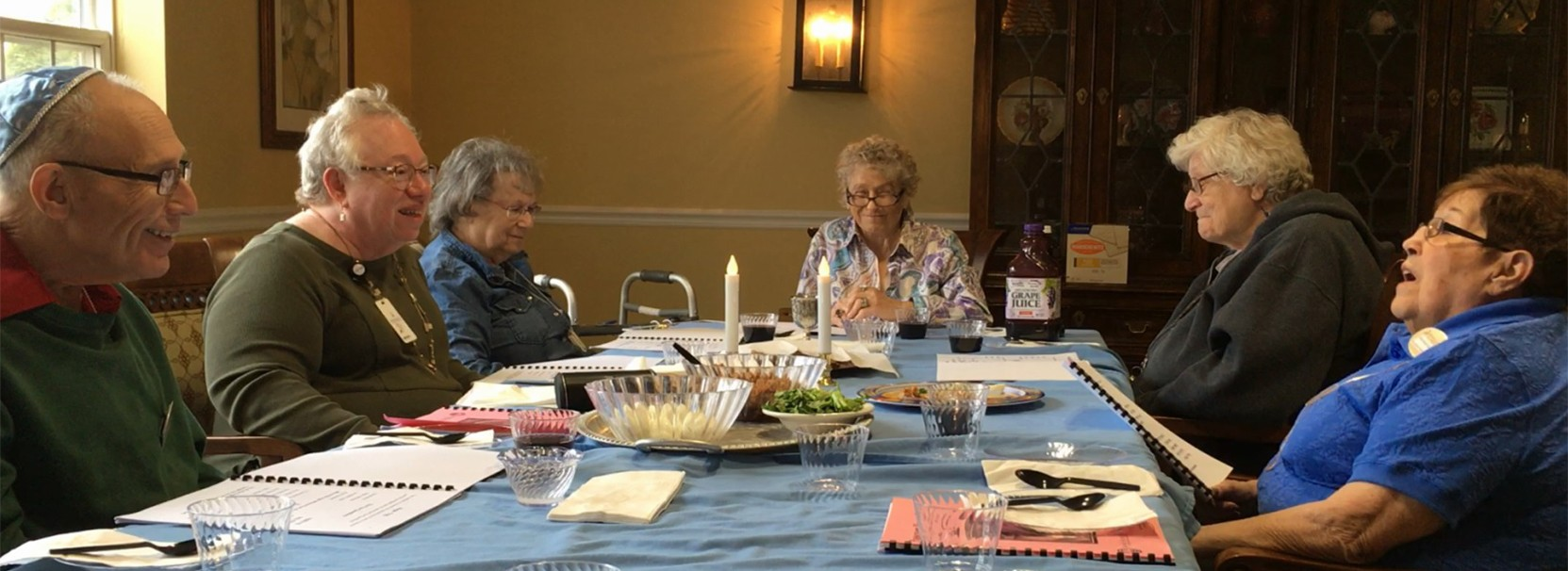 Group of five elderly people sitting around a table with Rabbi Bev having a Passover Seder