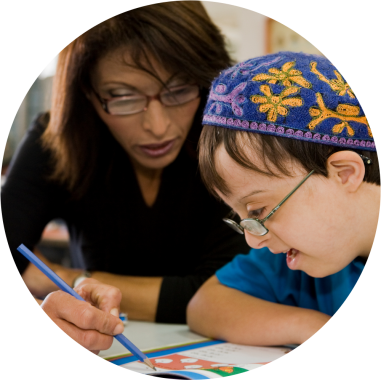 A Young Jewish boy with special needs and his teaching doing a worksheet