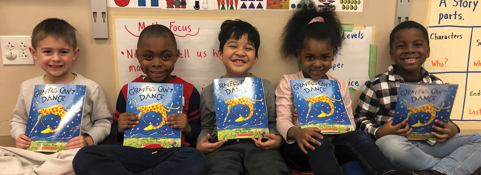 group of young students holding a book titled giraffes can't dance