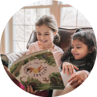 Two young girls smiling reading a J Library book together