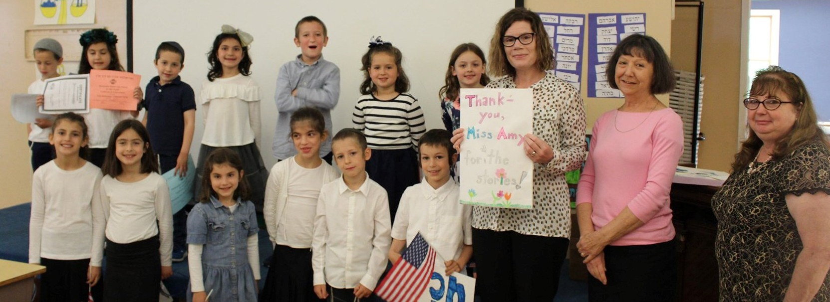 Miss Amy from PJ Library holding a thank you card from group of students gathered around her