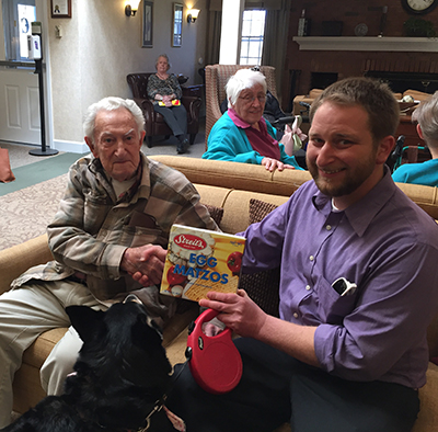 Young male volunteer with dog  handing matzah to an elderly man sitting on a couch
