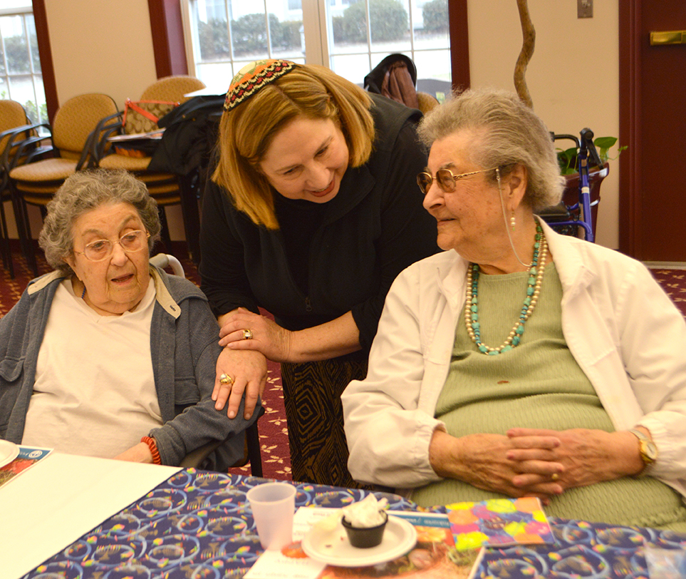 Woman chaplaincy volunteer bending over speaking with two elderly women sitting at a table