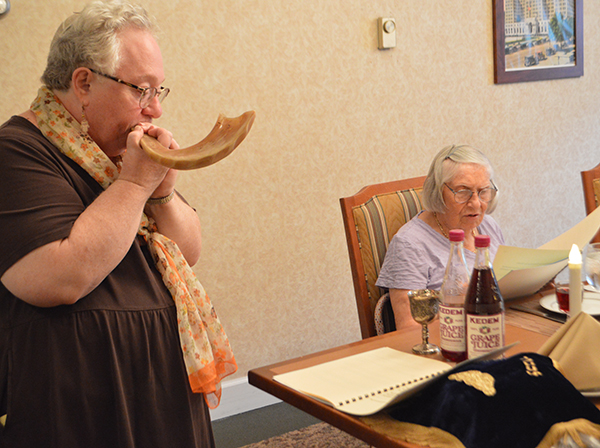 Rabbi Bev blowing the shofar, elderly woman sitting at table next to her