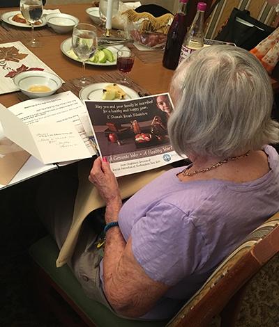 Elderly woman reading Rosh Hashanah card