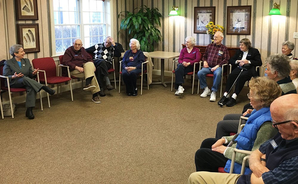 Group of elderly people sitting around the room having a discussion