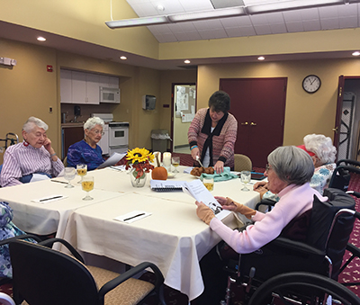 Woman chaplaincy volunteer cutting challah with four elderly women sitting around the table