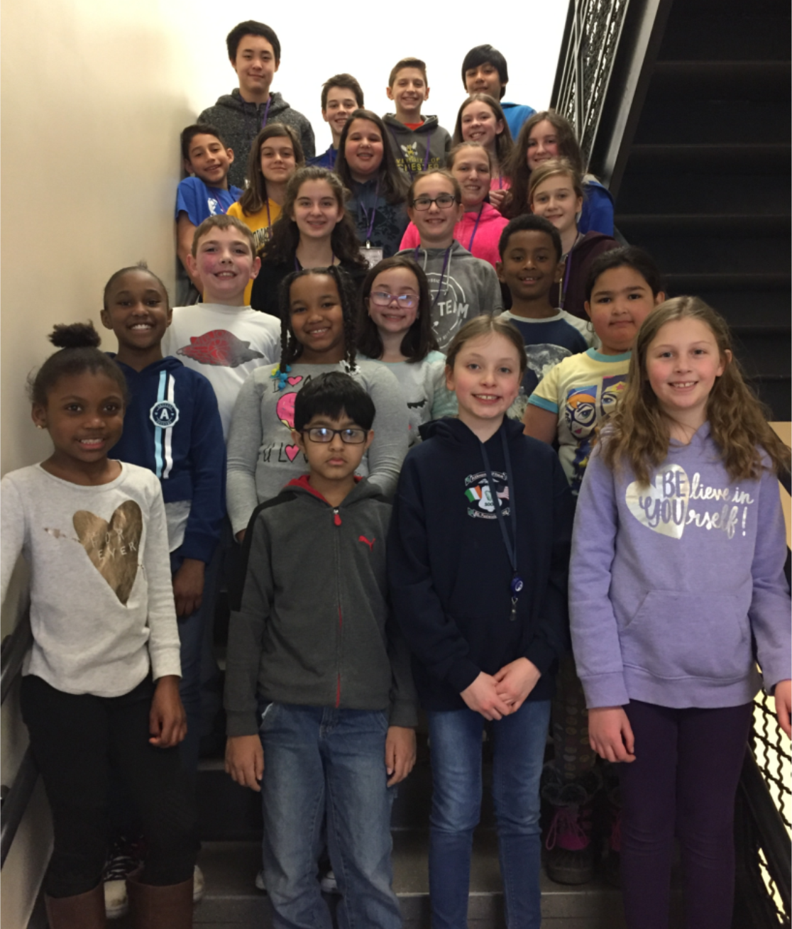 A large group of students standing on a staircase smiling for a group picture