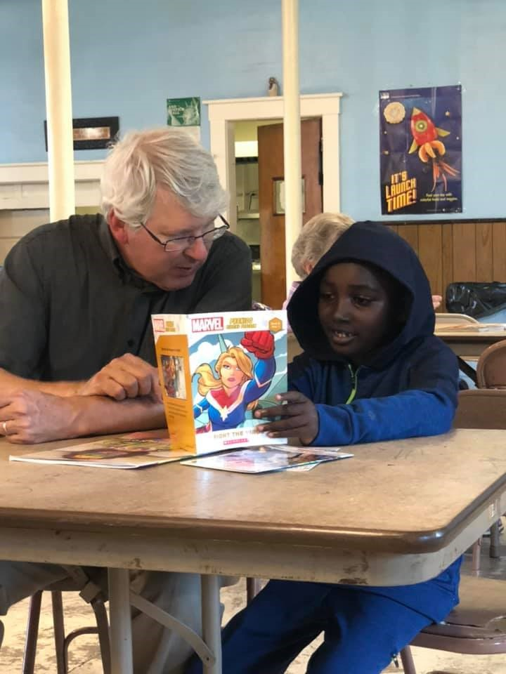 A Literacy volunteer reading with a student