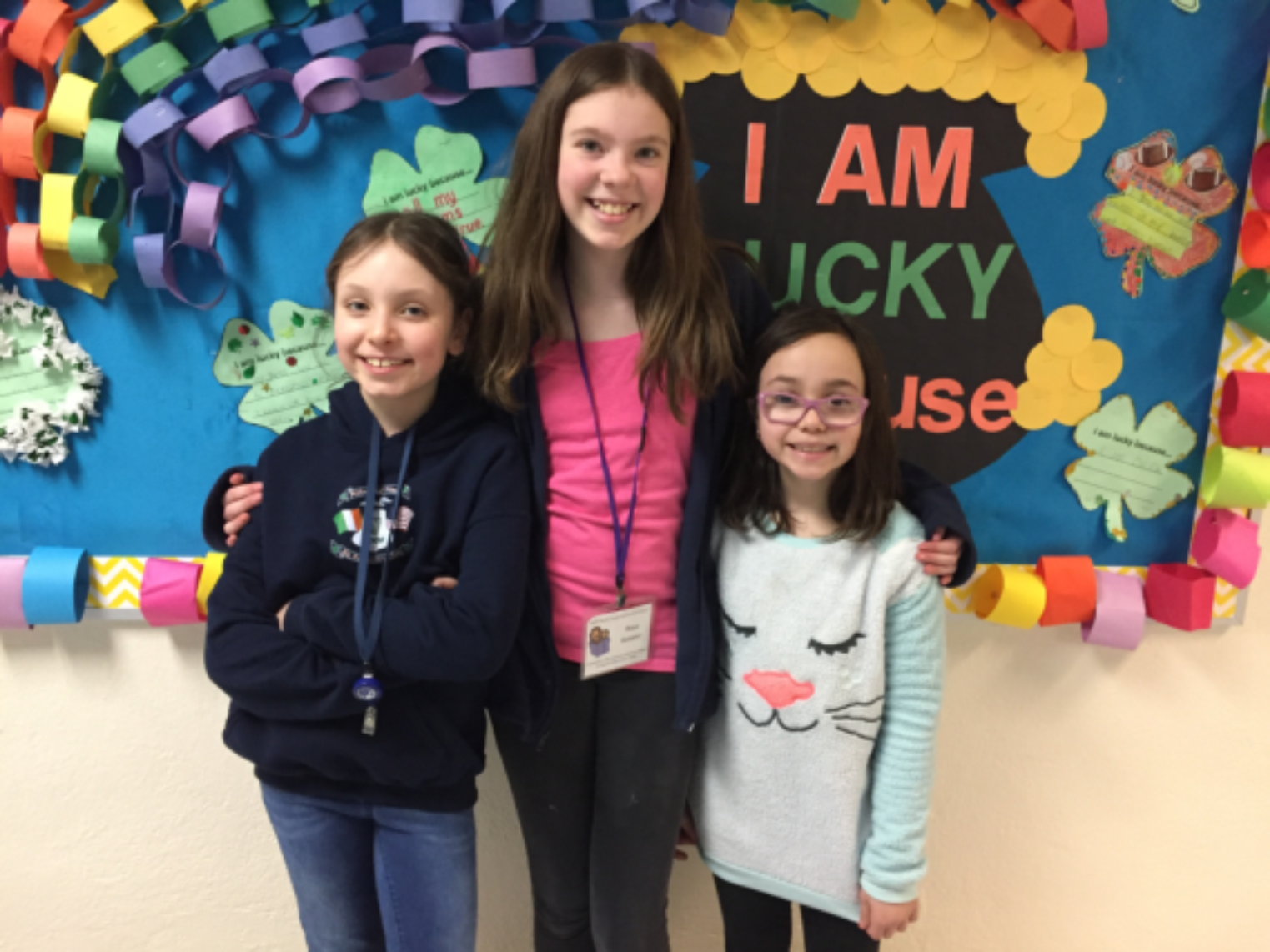 A young Literacy volunteer smiling with two young girls