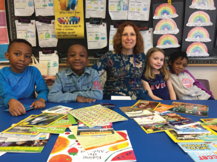 A Literacy volunteer with a group of four students smiling in front of a table of books