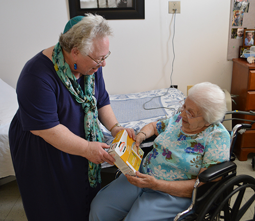 Rabbi Bev handing matzah to an elderly woman in a wheel chair