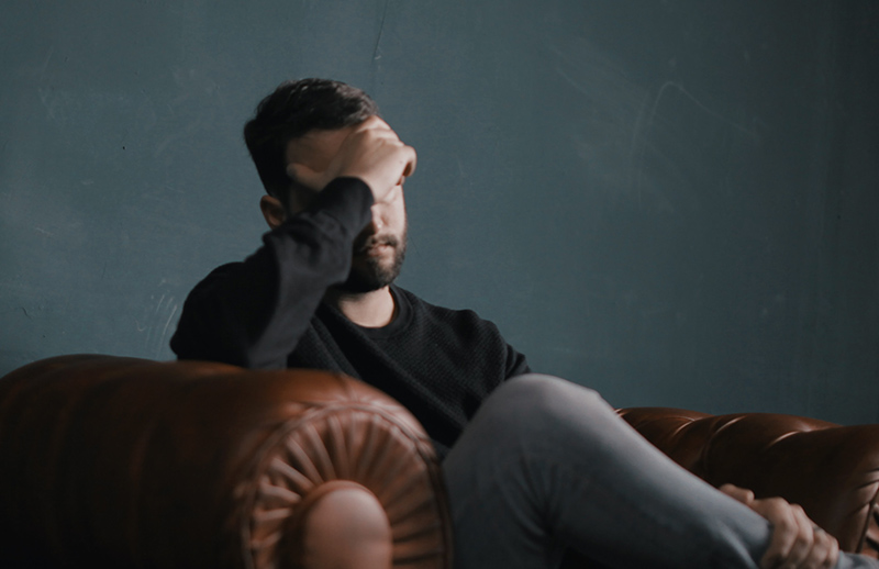 A man on a couch, covering his forhead with his hand